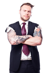Businessman in a suit with no sleeves and tattoo on his arms